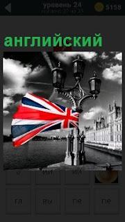 Изображение английского флага на фонарном столбе на фоне реки зданий на набережной