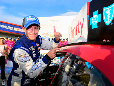 A J Allmendinger puts the Winner's Sticker on his car in Victory Lane after winning the NASCAR Xfinity Series Drive for the Cure 250 presented by Blue Cross Blue Shield of North Carolina at Charlotte Motor Speedway.
