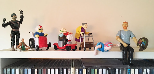 set of wind up toys depicting disability and art, sitting on shelf. photo by Artist and writer Corina Duyn