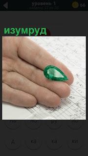 на ладони лежит драгоценный камень зеленого цвета изумруд
