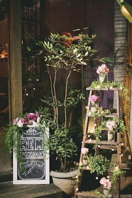 Boas vindas com escada de madeira enfeitada com flores e luzinhas