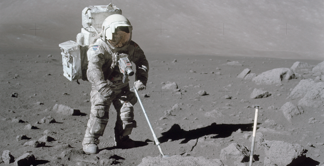 During an Apollo 17 EVA, lunar dusts is obviously seen to cling to astronaut Harrison Schmitt while he uses an adjustable sampling scoop to retrieve lunar samples. Efforts to understand the properties of lunar dust and to prevent its introduction into vehicles and habitats will minimize the risk of inhalation, dermal, and ocular injuries on future lunar missions. Credit: NASA/Eugene A. Cernan