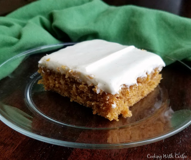 piece of pumpkin bars/cake with cream cheese frosting sitting on glass plate