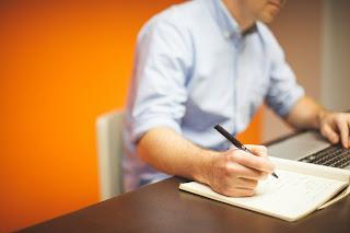 man writing home repair list
