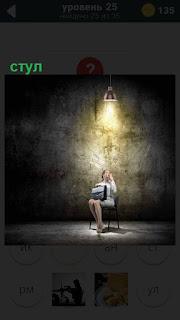 Под фонарем в пустом мрачном помещении на стуле сидит женщина с сумкой