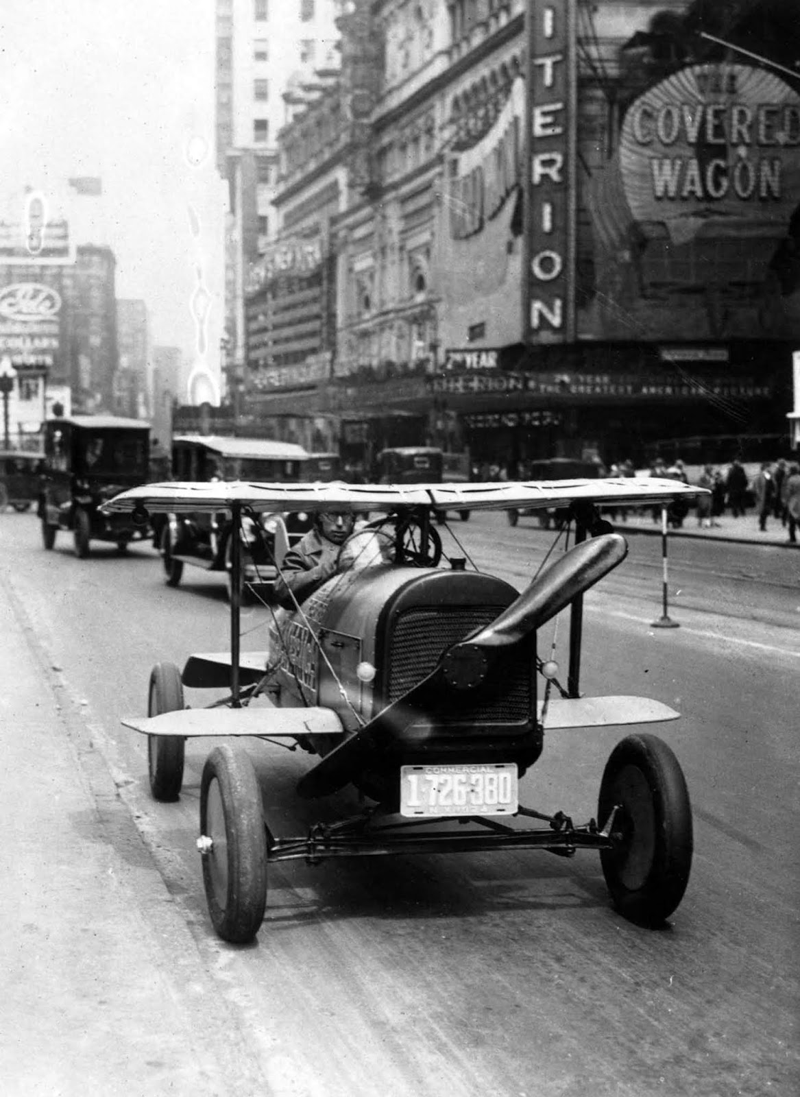 A car with wings and a propeller protruding from the radiator grille drives through Times Square, N.Y. It was the invention of A.H. Russell of Nutley, N.J.