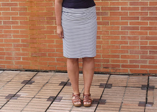 Modeling a white and navy blue striped knit pencil skirt against a brick wall.