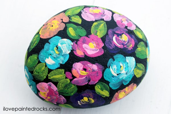 brush stroke flowers painted on a rock with a black background