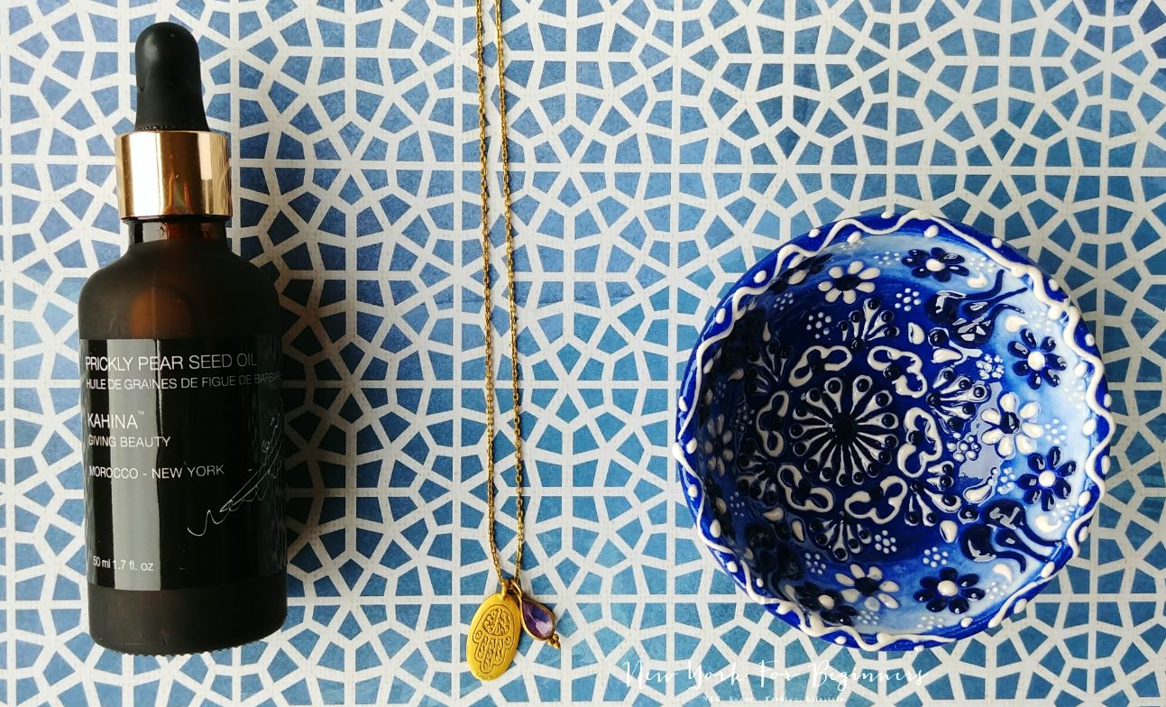 Kahina Giving Beauty Prickly Pear seed oil on a background of traditional Moroccan tiles and a necklace with a hamsa hand