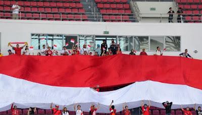 Suporter membentangkan bendera merah putih raksasa ketika menyaksikan pertandingan