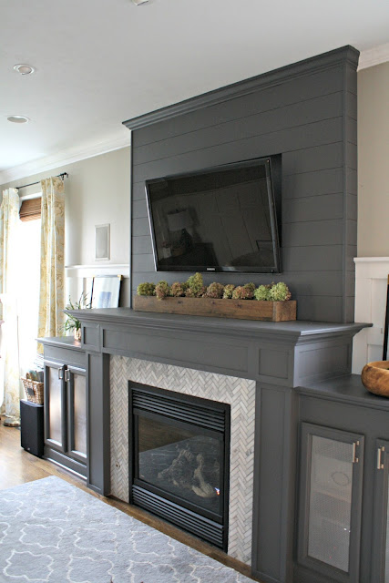 gray fireplace with herringbone marble tile