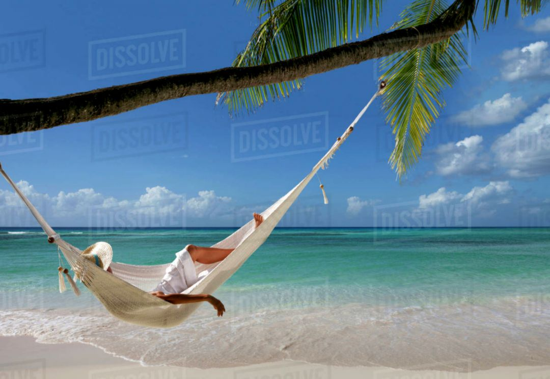 Caucasian woman laying in hammock under palm tree on tropical