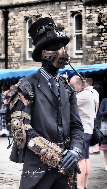 Steampunk man in top hat, suit, mask, top hat, goggles, black spandex second skin suit, gauntlet, bracer, and cane