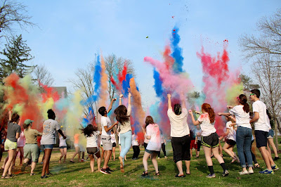 a group of students are outside throwing colorful powder up into the air. they are celebrating holi