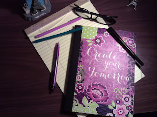 A simple collage on the surface of a desk.  A used yellow legal pad, a composition booklet with a decorative cover that is mostly shades of purple with a floral design, four different pens (colors purple, black, and green), a pair of black plastic framed glasses, and two Eiffel tower decorations that are going off frame.