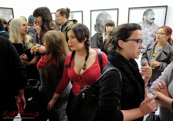 Red cardigan, deep cleavage plaited hair - pushing through the art crowd at China Heights Gallery.
