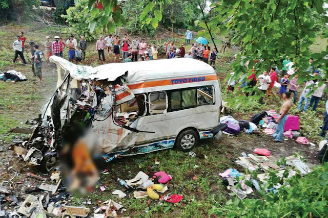 People gather around the wreckage of a Mekong Express minibus that was destroyed in a collision with a right-hand-steering truck that left nine dead in Battambang province on Monday. Photo