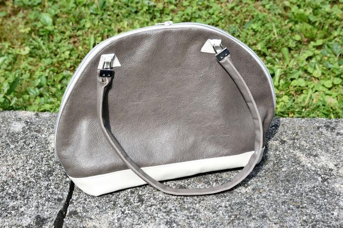 Vorderansicht der Tasche mit sichtbarem Träger, abgeschlossen mit Gurtbandklemmen und dreieckigen Patches