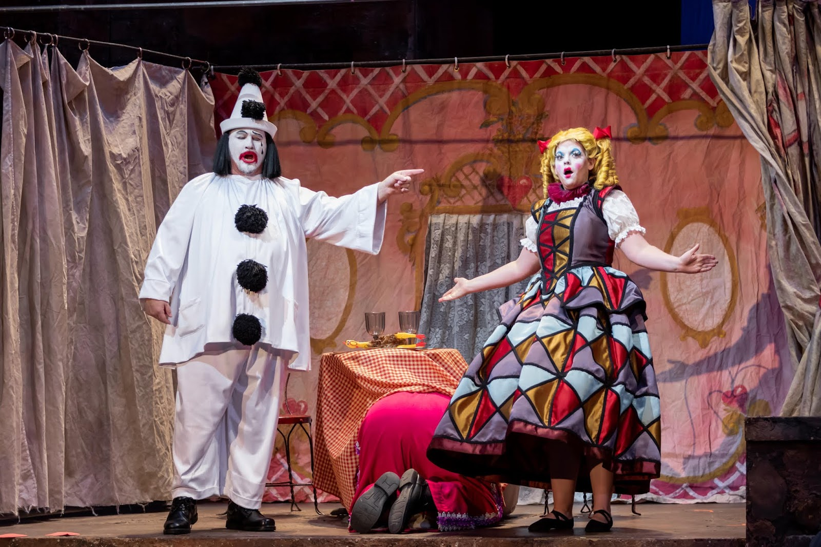IN REVIEW: (from left to right) tenor CARL TANNER as Canio, baritone KIDON CHOI as Tonio (hiding under table), and soprano MELINDA WHITTINGTON as Nedda in North Carolina Opera's January 2020 production of Ruggero Leoncavallo's PAGLIACCI [Photograph by Eric Waters, © by North Carolina Opera]