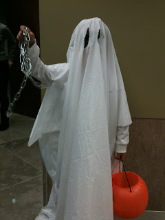 A Child in a bedsheet ghost costume with an orange pumpkin, ready to hunt for candy