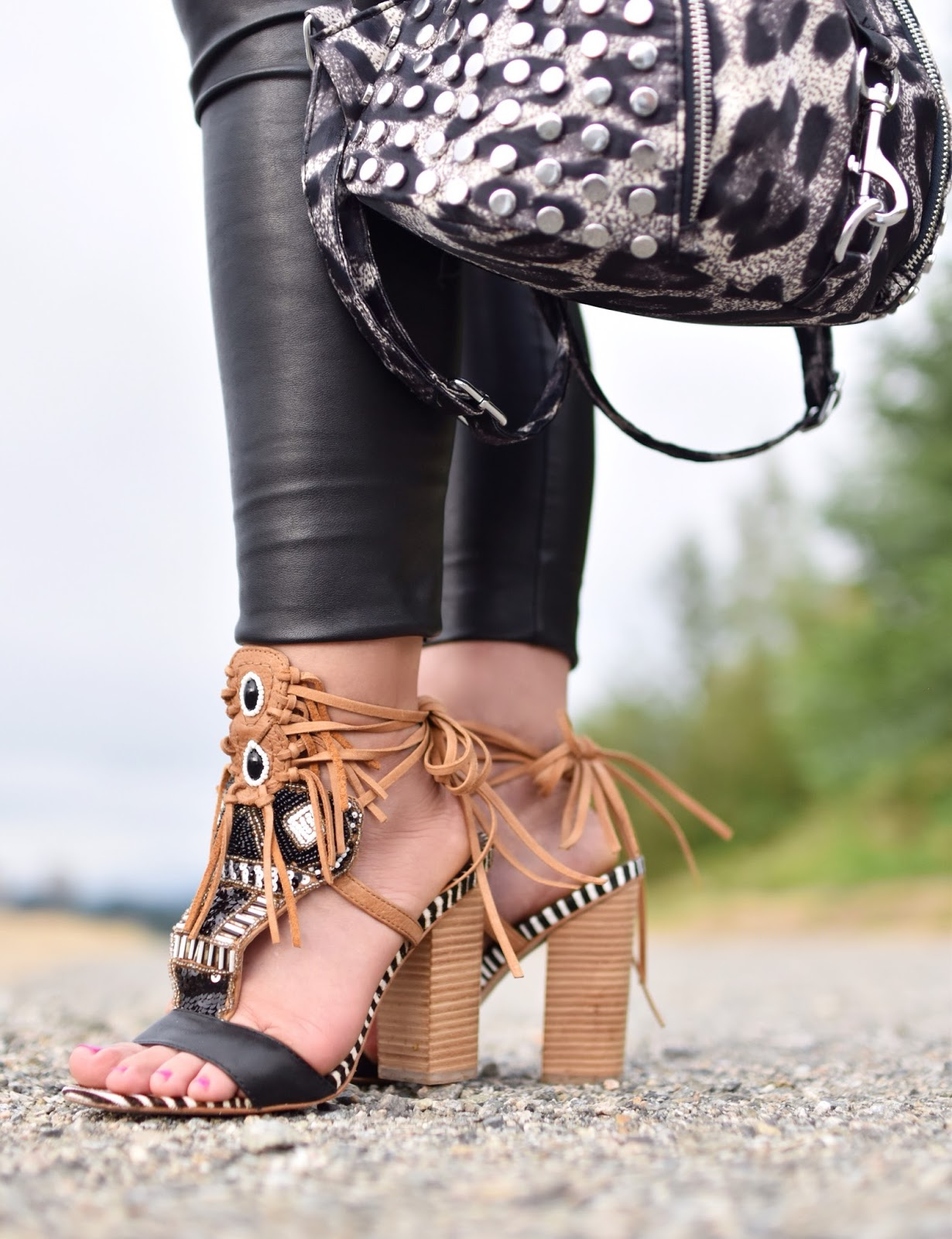 Monika Faulkner personal style inspiration - black vegan leather leggings, beaded fringe-embellished sandals, leopard-patterned backpack