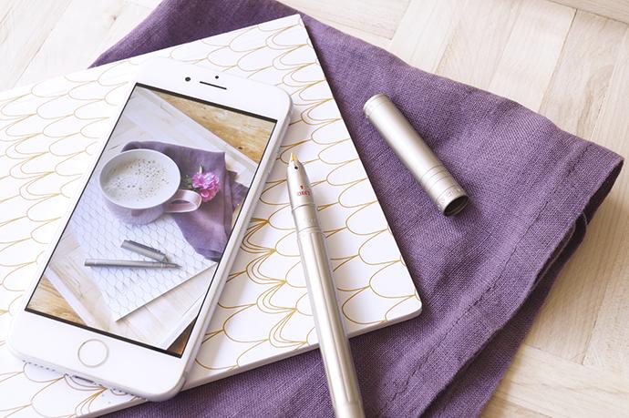 Handy und Schreibheft mit Stift auf Serviette und Holztablett.