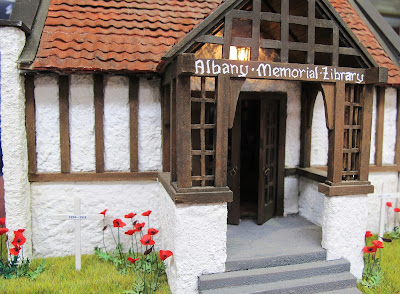 One-twelfth scale miniature arts-and-crafts library with poppies and crosses planted around it.
