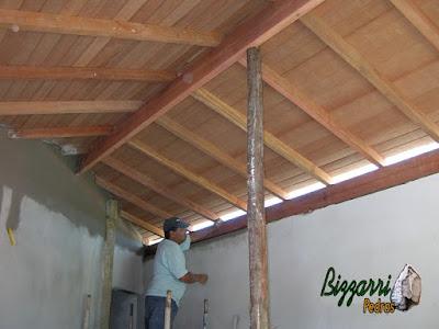Detalhe da execução do madeiramento com o forro de madeira por cima dos caibros com a massa desempenada e filtrada na parede em reforma da casa com a sala de estar e a suíte superior.