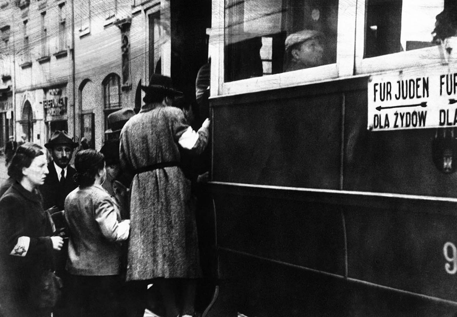 A scene from the Warsaw Ghetto where Jews are seen wearing white armlets bearing the Star of David and trams are seen marked with the words