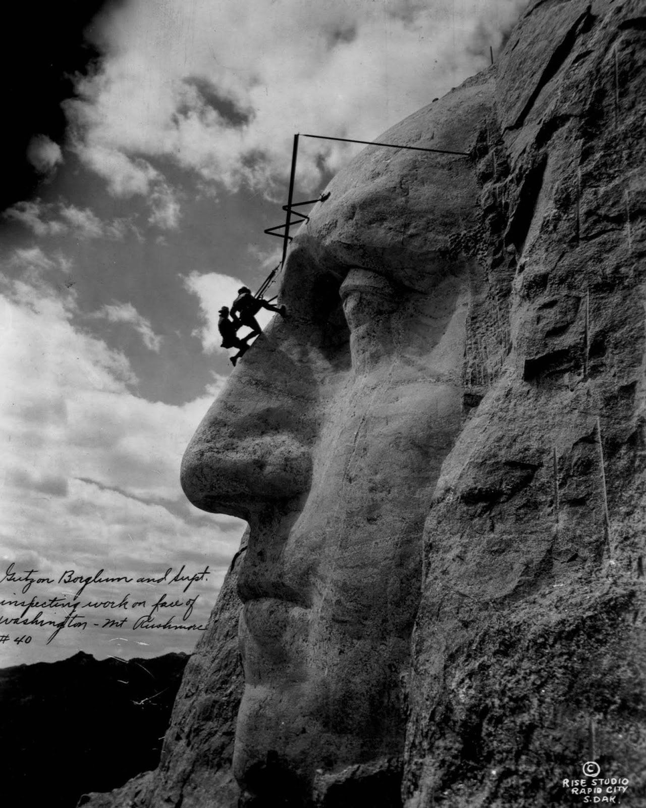 Gutzon Borglum and another sculptor hang from the forehead of George Washington. 1932.