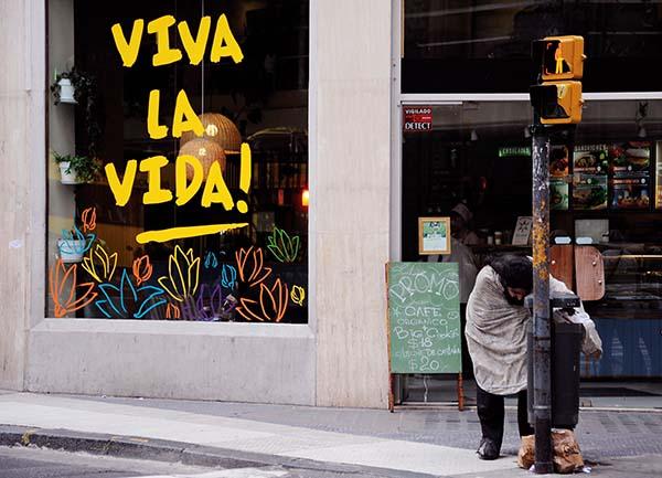 """Un hombre en situación de calle busca alimento en la basura, atrás en una vidriera, la inscripción """"Viva la vida"""""""