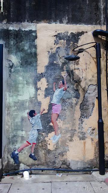 brother and sister playing basketball street art penang