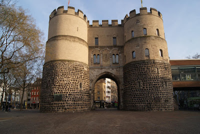 Ein burgartiges Gebäude mit zwei mächtigen Türmen rechts und links. In der Mitte ein hohes Durchgangsportal in Bogenform.