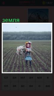 стоит девочка с венком на голове на засеянной земле