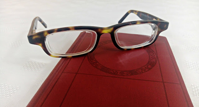 Eyejuster glasses, balanced on a small book