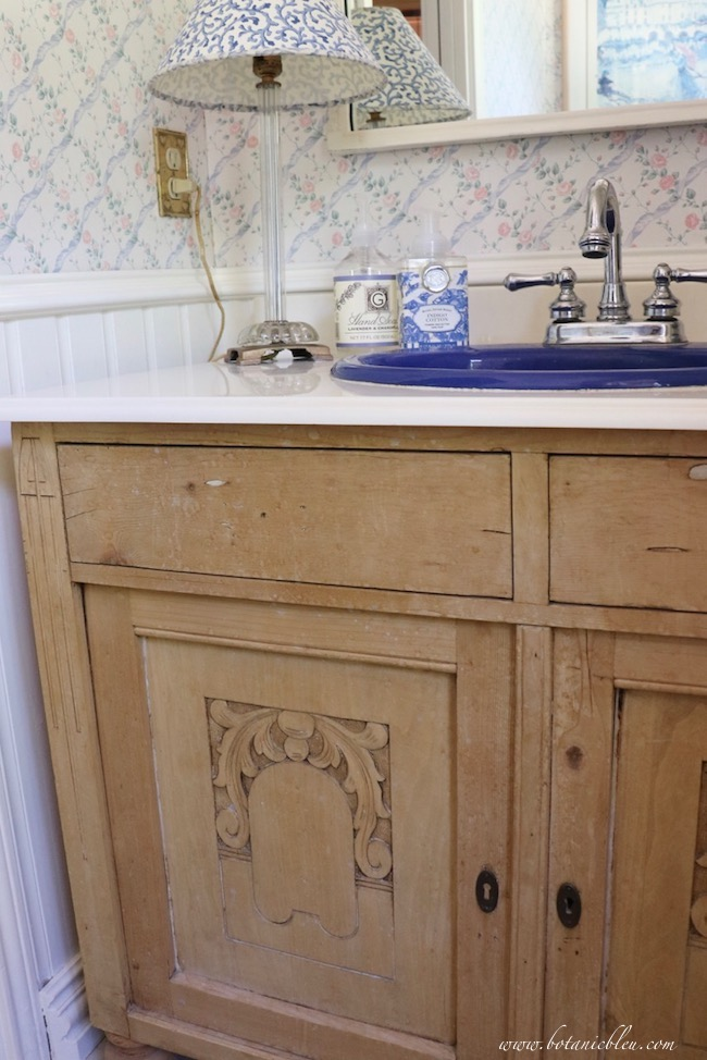 Budget wise cultured marble countertop with ogee edges and a porcelain sink in a vintage pine washstand