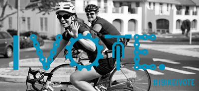 Black-and-white photo of woman and man, helmeted and on bicycles, wave to viewer as they pass in side-view through a city street. Superimposed are the words, 'I Vote' rendered in stylized blue letters out of bicycle chain length and head-on bicycle hande-bars and frame.' In lower right corner, superimposed in blue letters, '#IBIKEIVOTE'
