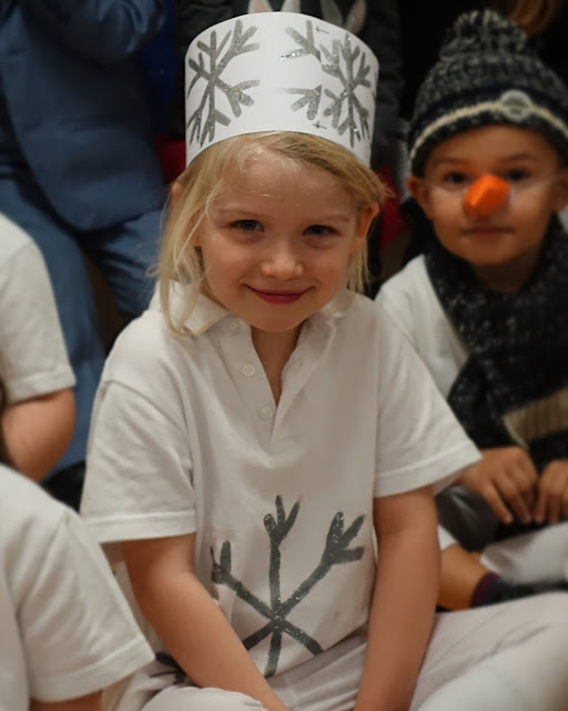 A 5 year old with a white t-shirt with a snowflake on and a white and silver snowflake hat