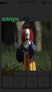 На поляне стоит клоун в соответствующей одежде и держит шарики