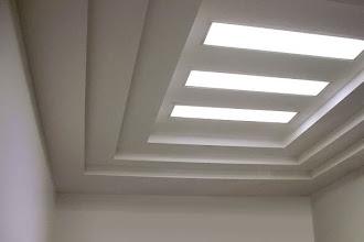 İç içe dikdörtgenler içinde üç uzun beyaz şerit aydınlatma olan kartonpiyer tavan