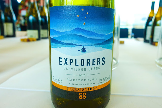 A close up of Explorers Sauvignon Blanc white wine this a person in a canoe and mountains in the background