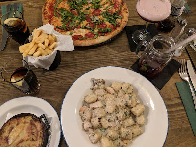 flatlay style image of pizza chips and gnocchi on a wooden table