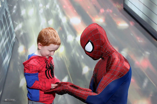 Little boy wearing a spiderman jumper whilst being shown how to do spidey hands by spider-man