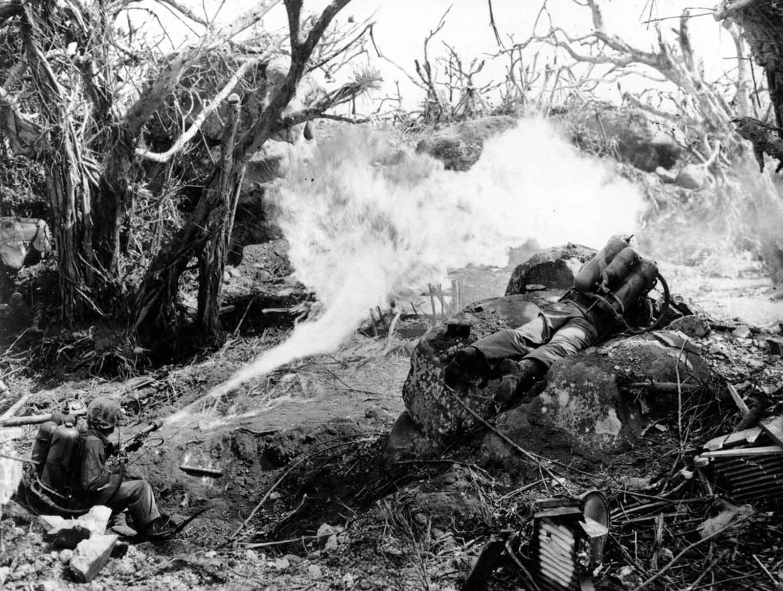 Two U.S. Marines direct flame throwers at Japanese defenses that block the way to Iwo Jima's Mount Suribachi on March 4, 1945. On the left is Pvt. Richard Klatt, of North Fond Dulac, Wisconsin, and on the right is PFC Wilfred Voegeli.