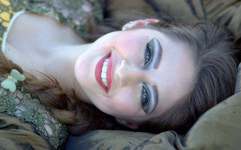 beautiful smiling woman with lots of eye makeup laying down.jpeg