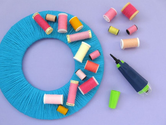 decorating the wreath with the upcycled thread reels