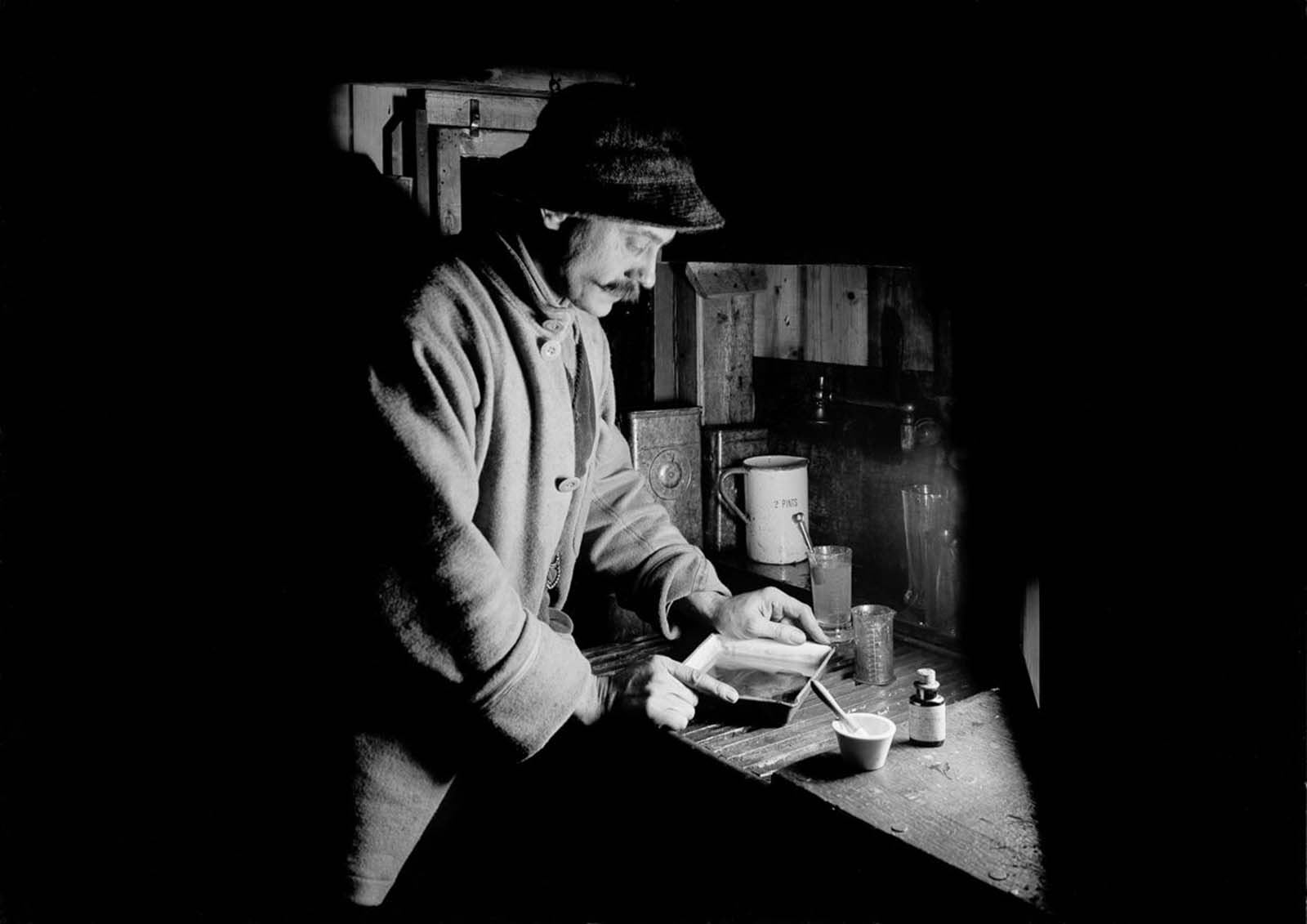 Photographer Herbert Ponting in his makeshift darkroom. July 22, 1911.