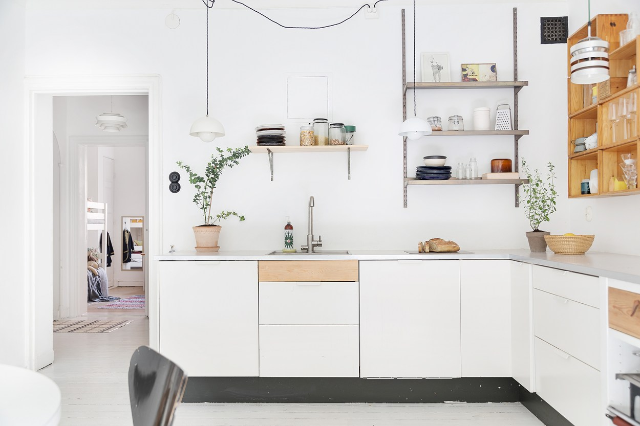 minimalist kitchen inside of a scandinavian farmhouse with white painted floors, midcentury modern lamps