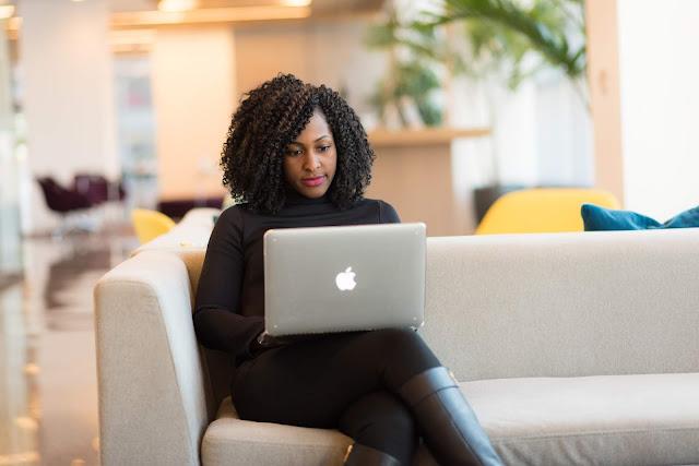 mujer de raza negra trabajando utilizando una computadora personal