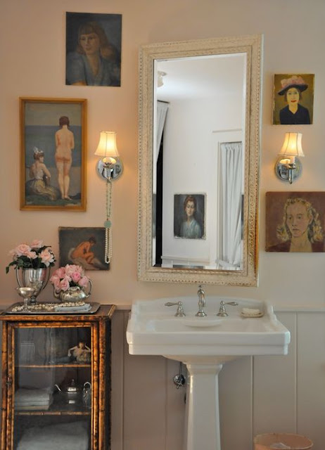 Romantic farmhouse pink walls in bathroom with vintage oil portraits by Brooke Giannetti